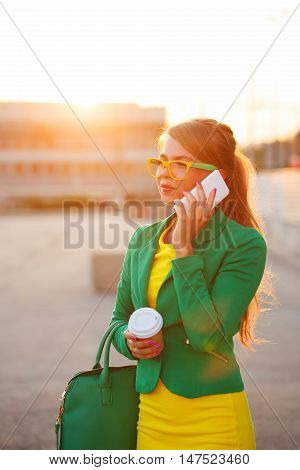 Young attractive woman talking on a cell phone. Businesswoman holding a cup of coffee and fashionable bag. A successful and positive. Soft focus.