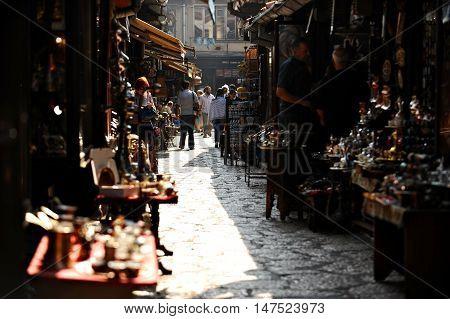 BOSNIA SARAJEVO - AUGUST 27 2015: Tourists looking at souvenirs in old Sarajevo bazaar on August 27 2015 in Sarajevo.