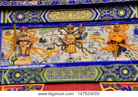 Sui Ning China - March 14 2015: Carved painted figures decorate a panel on the great Ceremonial entrance gate at the Guang De Si Buddhist Temple *