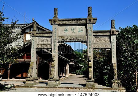 Xin Xing Zhen China - March 24 2012: An imposing ceremonial entrance gate inscribed with Chinese characters leads into the town's main street