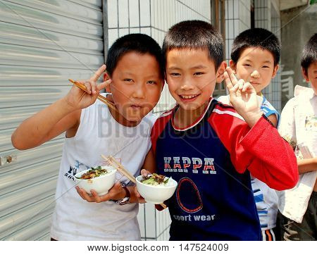 Wan Jia China - June 12 2007: A group of little Chinese boys eating their lunch from small rice bowls in front of their school