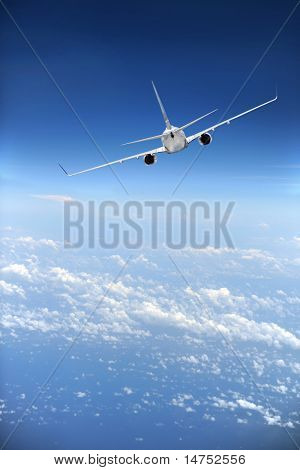 Jet airliner in flight with clouds in the distance