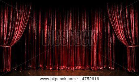 Cortinas de palco vermelho sobre o piso de madeira
