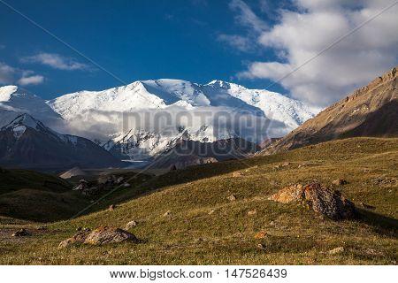 Rocks, grass, and summit of the Lenin peak. View from base camp Achik-Tash. Pamir region. Kyrgyzstan