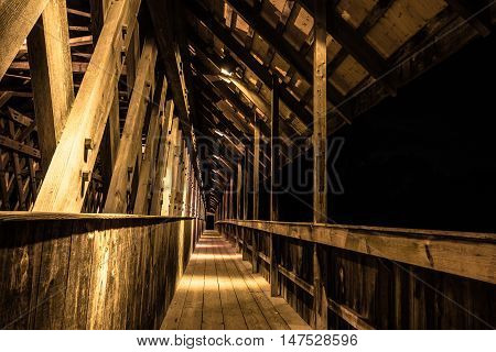 Forward Into The Darkness. . Pedestrian walkway of a wooden bridge leads into the darkness. Frankenmuth, Michigan.