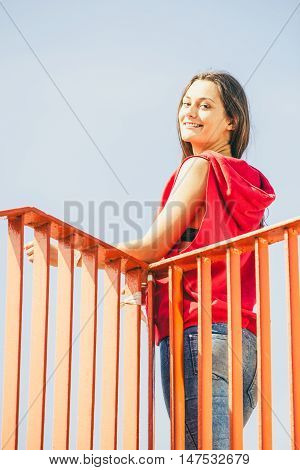 Young long haired girl leaning against railing on a walk the urban bridge. Lifestyle funky in summer. Trendy sport teen.