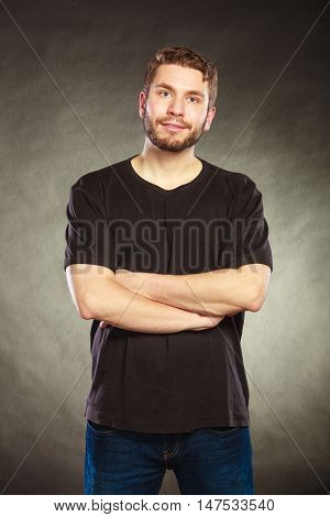 Portrait of handsome fashionable man in blank shirt. Young guy posing in studio on black. Casual fashion.