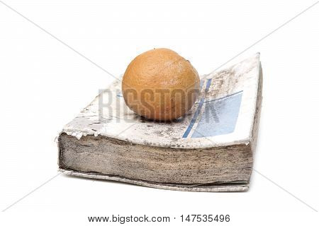 An old book with a rotten orange