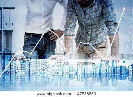 Two brokers standing in their office. Large forex graph and city panorama at the foreground. Concept of trading. Double exposure