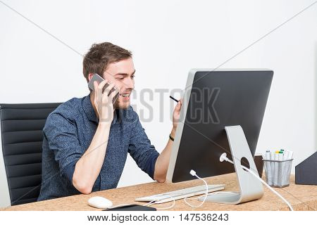 Businessman using his phone and looking at computer screen smiling. Concept of good deal.
