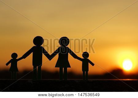 Paper cut of family with sunset background / Family Life Insurance / Protecting family / Family concepts