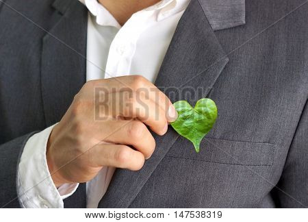 Businessman holding a green heart leaf / Business with corporate social responsibility and environmental concern