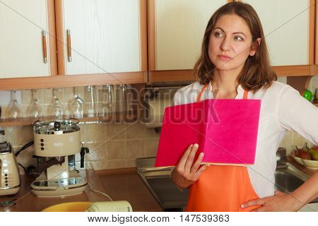Mature thoughtful housewife cook chef holding cookbook looking for recipe. Middle aged woman preparing food in kitchen.