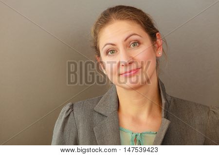 Middle aged smiling business woman wearing stylish jacket. Mature female in elegant outfit in serious office work. Corporation concept. Studio shot.