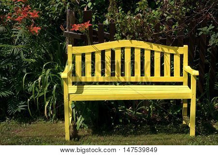 Yellow wooden bench in a garden or park setting.