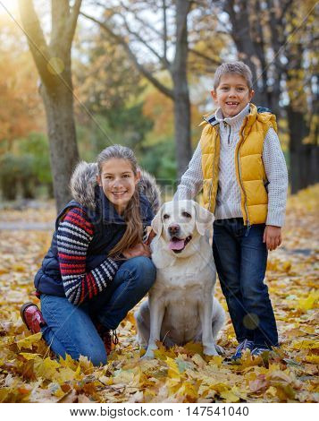 Cute kids and dog Labrador retriever posing in autumn park. Yellow and orange leaves around.