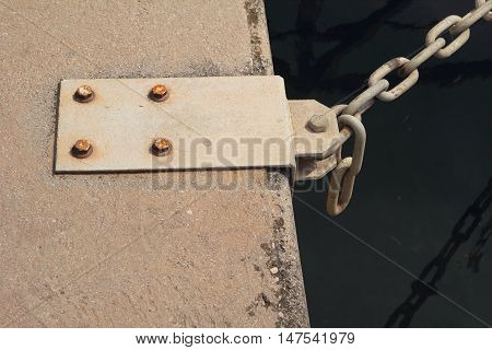 Steel mooring point on quayside with chain attached