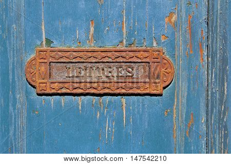 Traditional French rusty iron letter box on grungy blue flaky painted wooden door