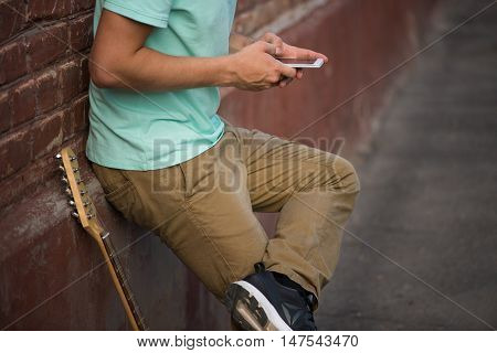 Young stylish guy should have a brown brick wall, hands holding cell phone next to the guitar.
