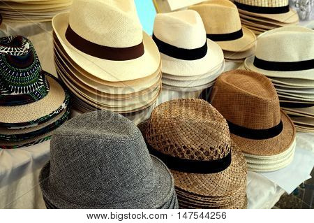 Straw Fedora Hats For Men In Varied Colors And Designs On A Market Stall