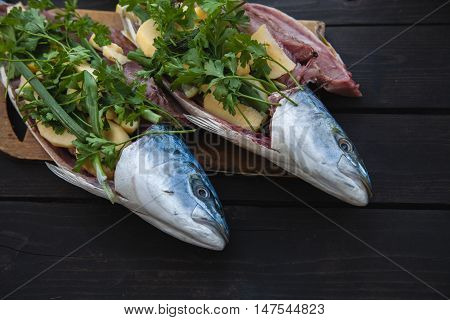 Fresh Fish on wooden background. Yellowtail Amberjack. Stuffed with apples, lemon and fresh herbs