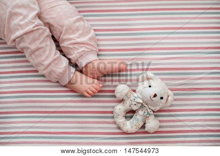 baby leg on the striped background. the view from the top. on bed at home about a favorite toy