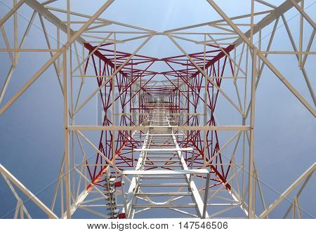 Newly completed telecommunication tower with white and red paint step ladder in blue sky as background.