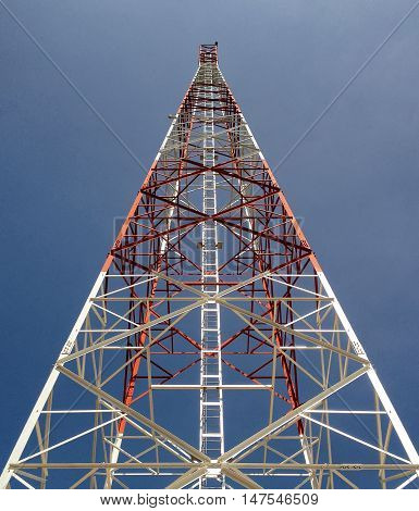 Newly completed telecommunication tower with blue sky as background.
