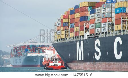 Oakland CA - September 12 2016: Tugboat VALOR off the port bow of MSC ARIANE assisting the vessel to maneuver into the Port of Oakland the fifth busiest port in the United States.