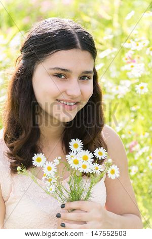 Girl teenager with bouquet of daisies on a summer meadow