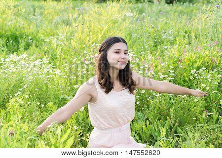 Teenage girl resting on a flower meadow