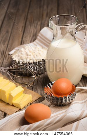 Ingredients for baking - milk, butter, eggs and flour. Rustic background, selective focus, copy space.