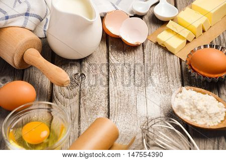 Ingredients for baking - milk, butter, eggs and flour. Rustic background, top view, copy space.