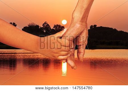 hand little kid hold hand old man at sunset river background