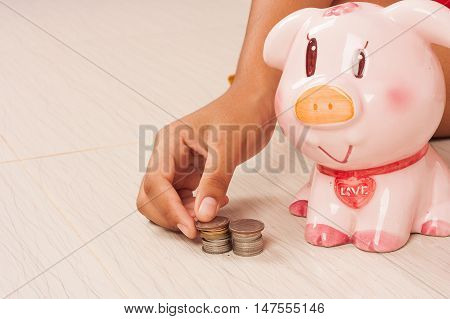hand gril saving money in piggy bank concept