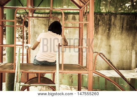 cute asian girl sitting alone at playground