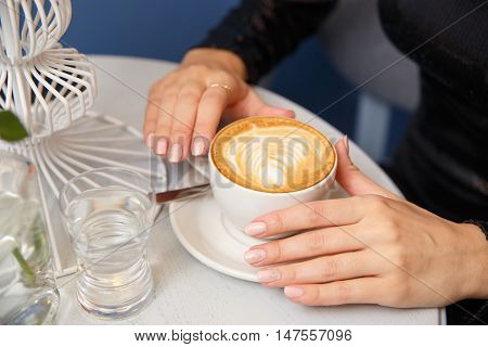 Close-up female hands holding cup with coffee cappuccino with foam with pattern heart. Perfect creative manicure. Wood natural table.