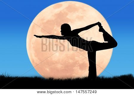 Silhouette young woman practicing yoga on full moon background