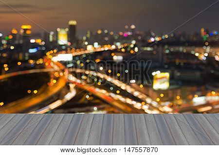 Open wooden floor, blurred lights night view highway intersection with city downtown background