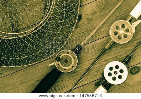Fishing accessories for winter. Tackles and net. Wooden background. Outdoor activity and leisure concept. Toned.
