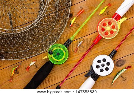Fishing accessories for winter. Tackles bait lure jig hook net. Wooden background. Outdoor activity and leisure concept.