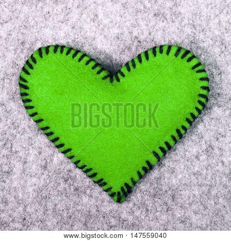 green felt heart on a gray background