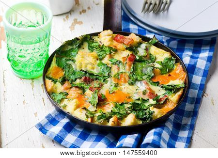 Skillet Strata with Bacon Cheddar and Greens . selective focus