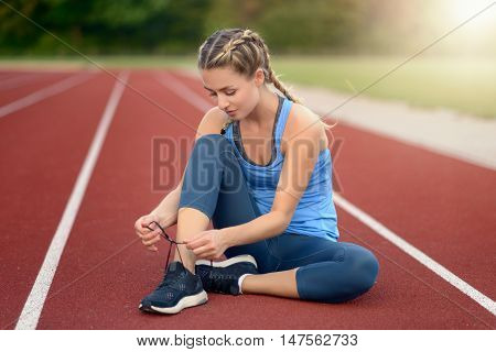 Sporty Young Woman Sitting On A Race Track