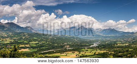 Champsaur Valley and Drac River with clouds. Hautes-Alpes (Southern French Alps) in summer. The panoramic view includes the mountain peaks: Palastre, Soleil Boeuf, Touron Peak, Grande Autane, Petite Autane and Aiguille. France