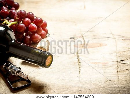 Red wine with a corkscrew, grapes and corks. On wooden background.
