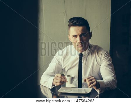 Man young handsome elegant model wears white shirt black skinny necktie sits at table holds cup of coffee and looks in camera indoor on grey background