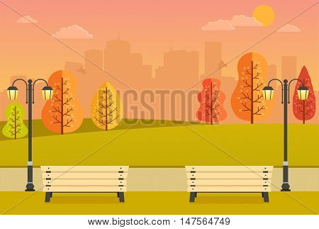 Beautiful autumn park with benches yellow and orange trees and city views. Evening park at sunset.