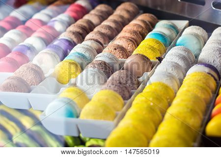 traditional french colorful tasty macaroons in a rows in a box in shop window