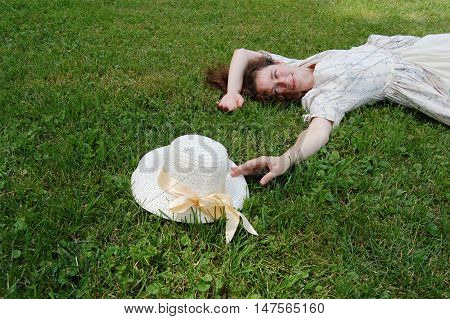 European woman laying on grass and touching hat in vintage. White color, curly hair, sensitive, sensuality.